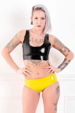 A woman wearing a latex outfit with yellow latex panty briefs.