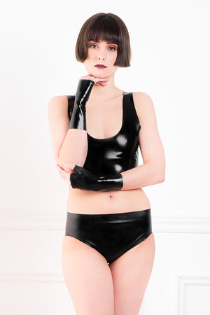 A woman wearing a black latex crop top and latex panty briefs with clit stimulator.