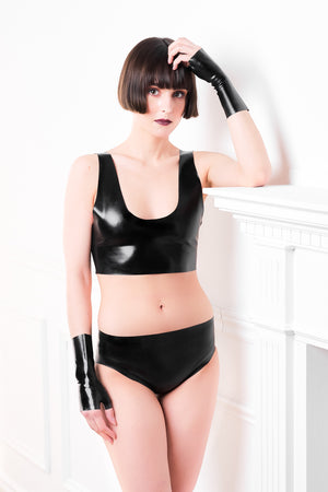 A woman leaning by a fireplace wearing latex underwear with clit stimulator, a black latex crop top and fingerless latex wrist gloves.