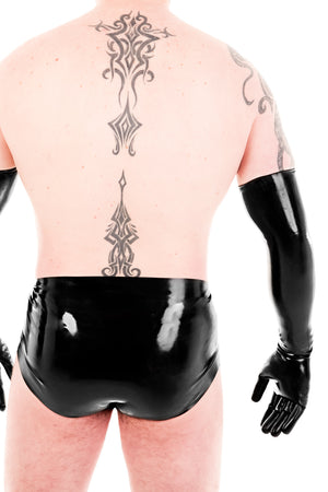 A man wearing black latex shoulder gloves and latex underwear. A rear view, showing his ass.