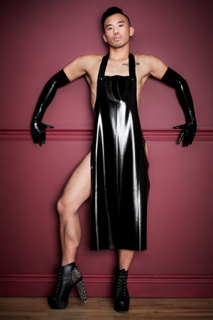 A man wearing latex shoulder gloves, heels and a black latex apron.