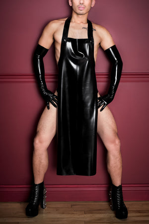 A man wearing black latex shoulder gloves and a full length latex apron, while in heels.