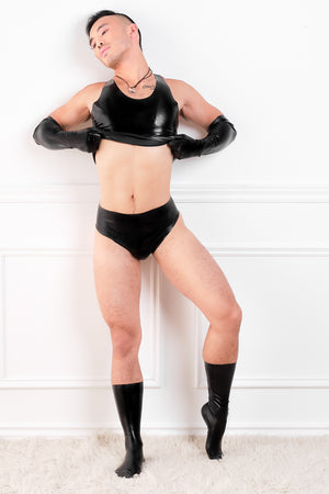 A man wearing black latex socks, latex elbow gloves, a latex top and underwear.