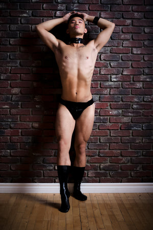 A man leaning against a brick wall wearing a latex thong and latex socks.