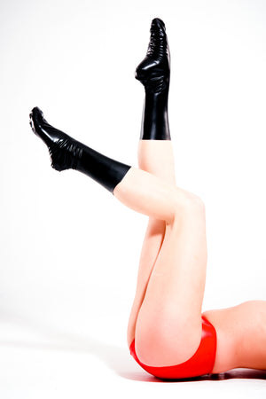A woman wearing black latex socks and red latex panties.