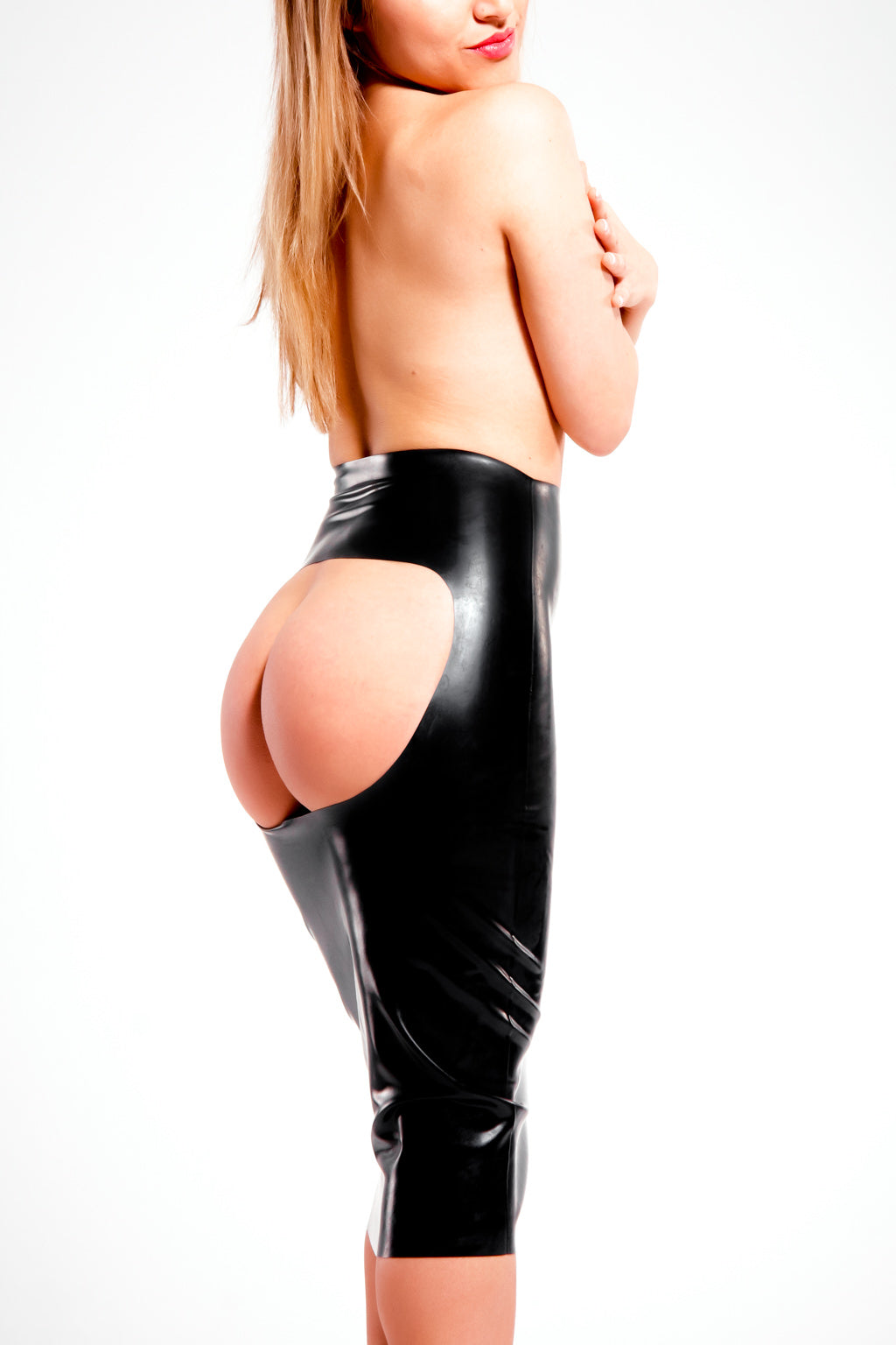 A woman wearing a black latex spanking skirt. A rear view, showing her ass.