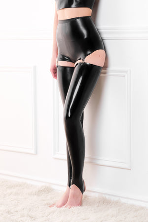 A woman wearing a black latex pantie girdle with a pair of latex stockings.