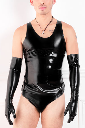 A man wearing a black latex shirt, latex elbow gloves and latex briefs.