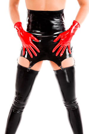 A woman wearing red latex wrist gloves and a high waisted latex garter belt with latex stockings.