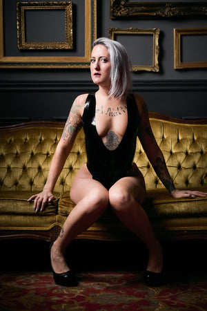 A woman sitting on a fancy couch wearing a latex leotard.