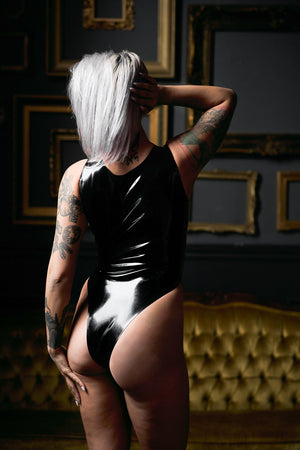 The back of a woman wearing a black latex bodysuit.