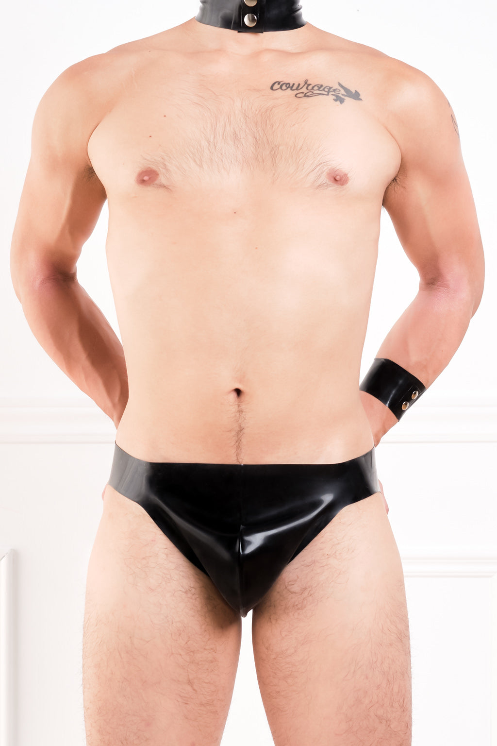 A man wearing a black latex thong.