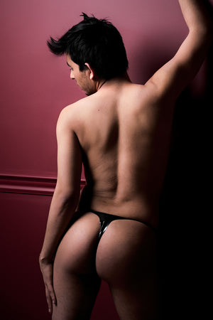 A man wearing a black latex thong. A rear view, showing his ass.
