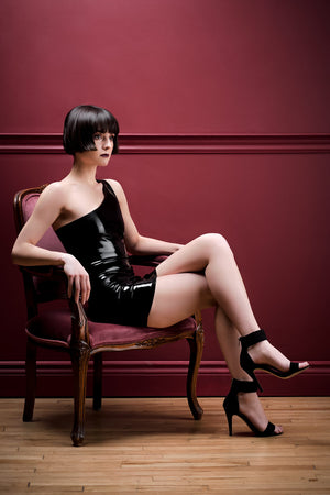 A woman sitting on a chair wearing a one shoulder latex mini dress.