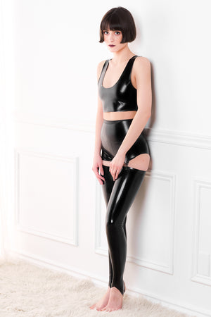 A woman wearing a black latex crop top and a latex pantie girdle with latex stockings.