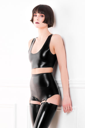 A woman wearing a black latex crop top with a latex pantie girdle and latex stockings.