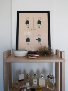 Photoshoot of a light pink illustration in a black frame displayed on a wooden shelf