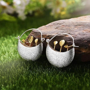 These 925 Sterling Silver Hoop Earrings with a silver planter box with gold plants coming out of them.