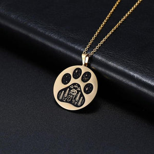 Gold pendant necklace with a paw engraved on it showing stars and a cat and dog in an outdoors scene