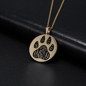 Gold pendant necklace with a paw engraved on it with a human and dog in an outdoors scene