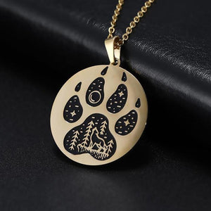 Gold pendant necklace with a paw engraved on it showing stars and a wolf howling in an outdoors scene.