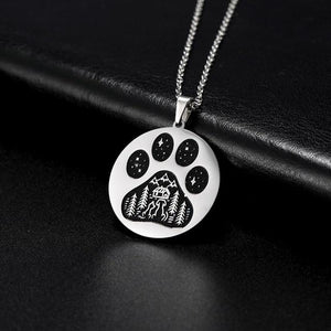 Silver pendant necklace with a paw engraved on it showing stars and a cat and dog in an outdoors scene