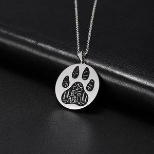 Silver pendant necklace with a paw engraved on it with a human and dog in an outdoors scene