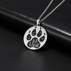 Silver pendant necklace with a paw engraved on it showing stars and a wolf howling in an outdoors scene.