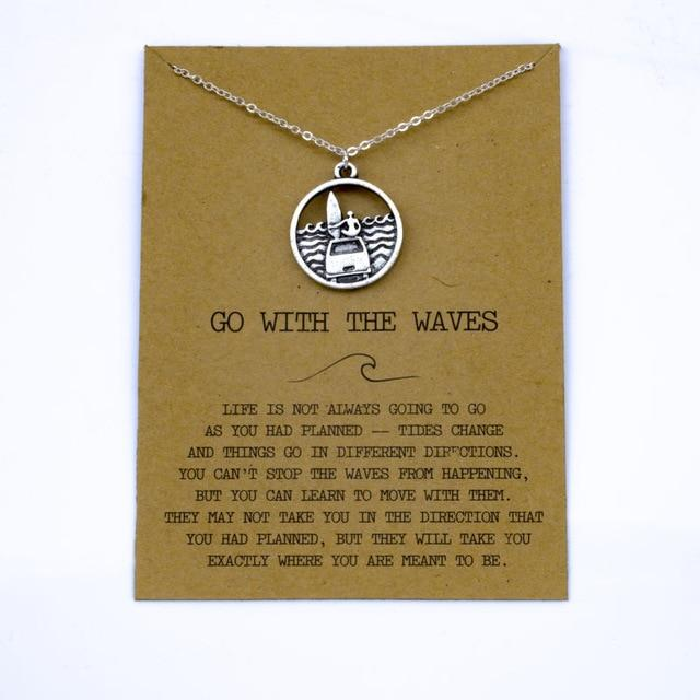 Silver necklace displaying a surfer on top of his van with a surfboard watching the waves