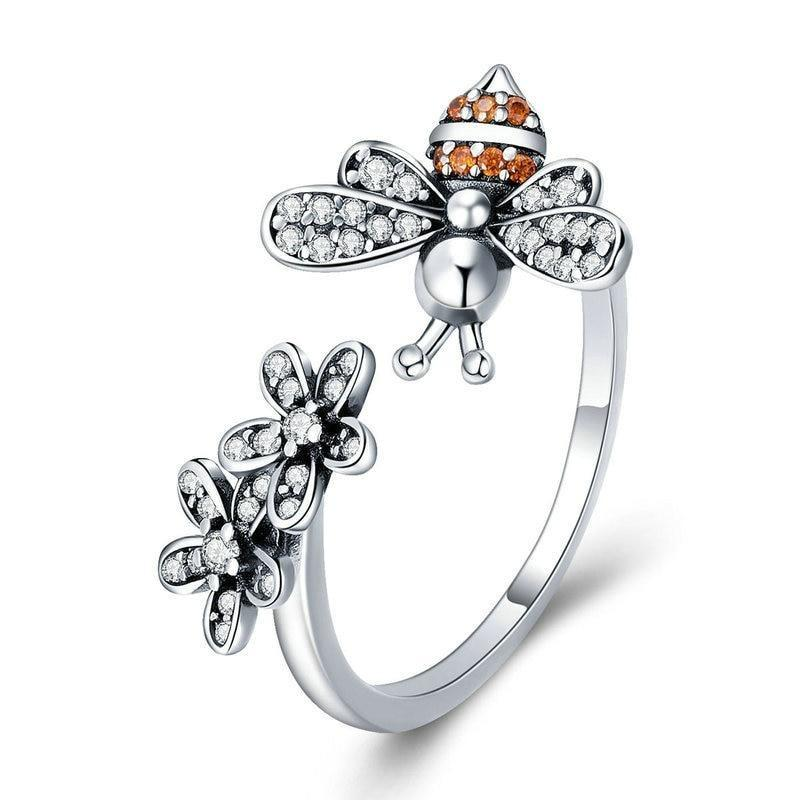 A 925 sterling silver bumble bee and flower adjustable ring made with cubic zirconia to allow it to sparkle displayed on a white background.