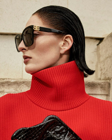 Woman wearing big sunglasses and red jumper