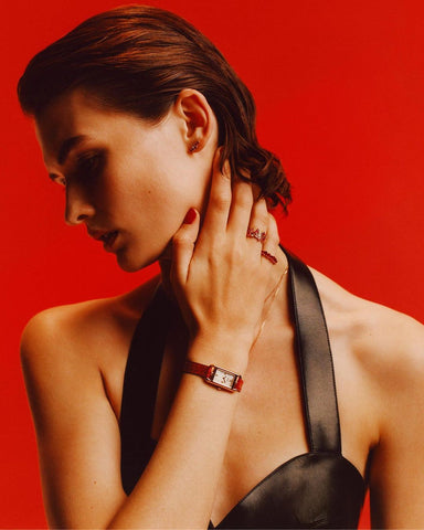 Model on red background showing off jewellery