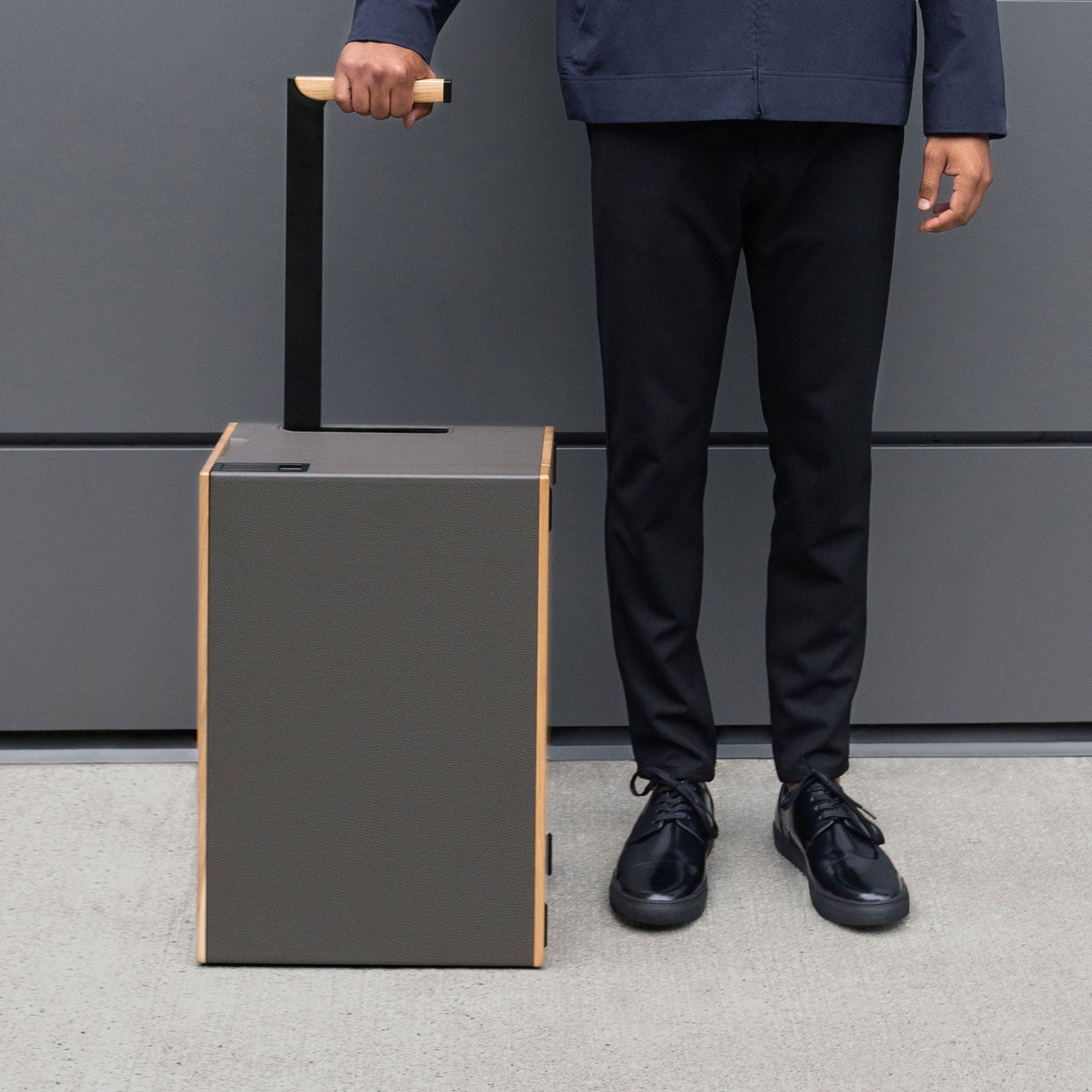 Man with a rolling suitcase in leather and aluminum