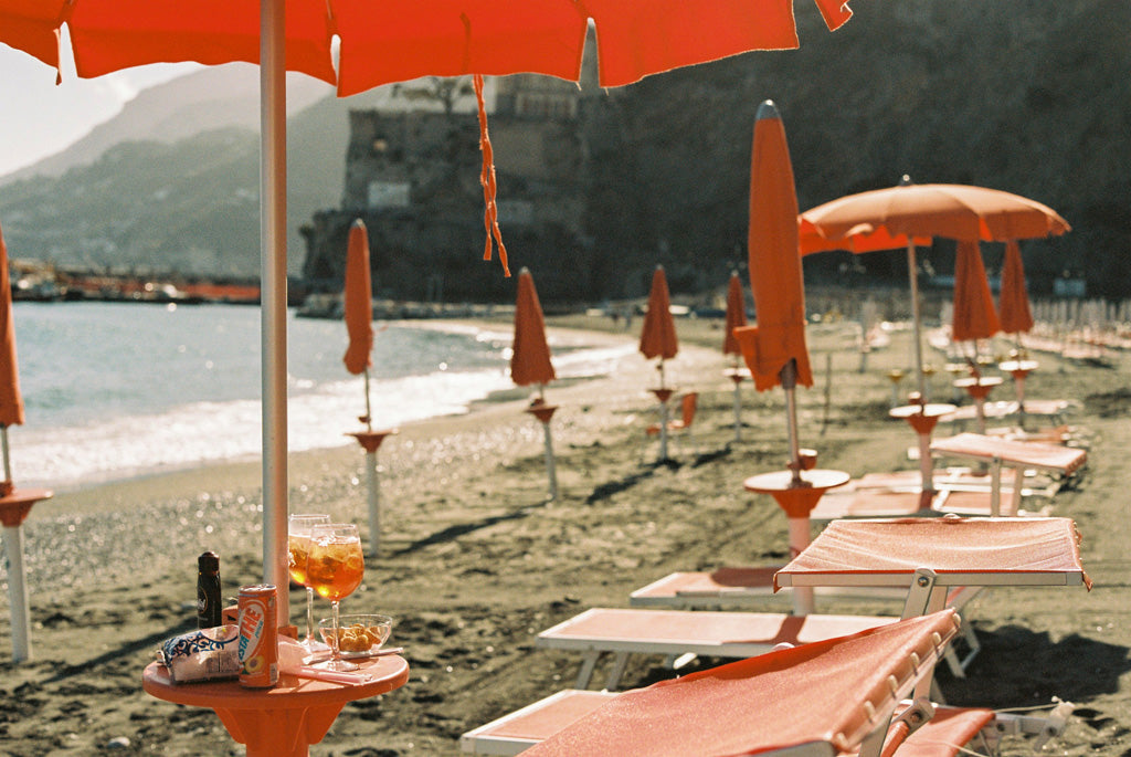 red sun beds on Italian beach with aperol