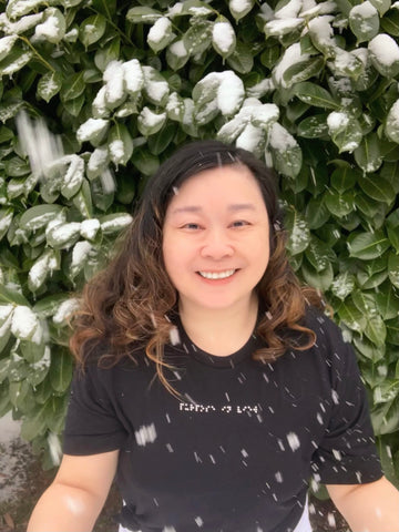"Anne is wearing her Aille Design custom braille black t-shirt ""purpose in view"" and smiling in the snow."