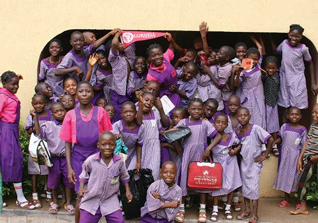 a group of orphans smiling standing outside of the abode for children - nigerian orphanage
