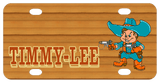 Name on left in shadowed text with cowboy with big rimmed cowboy hat holding pointed guns in both hands on right. Wood tone background and cowboy is dressed in blueish teal and rusty orange