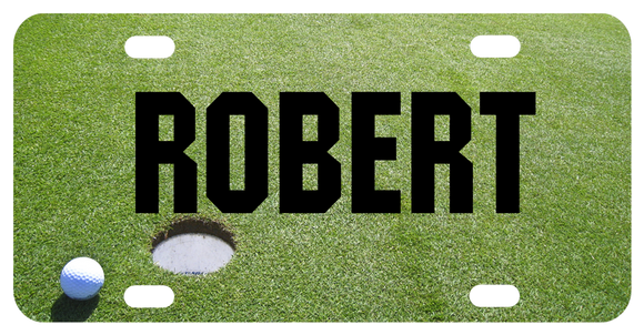 Personalized vanity license plate with golf ball next to hole on green custom printed with any name