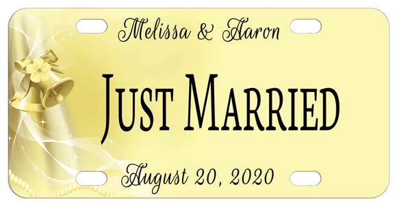 soft yellow goldish background with wedding bells, lace and pearls on the left of the plate and personalized text on top, center and bottom of license plate. Center says Just Married but can be custom printed with any text
