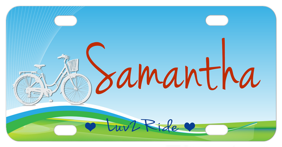 bike with basket on a hill claiming you luv 2 ride but you can personalized this custom bike plate with any text.