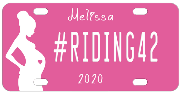 Pink Background with silhouette of a pregnant woman with a pink heart in her belly. Our sample reads #riding42 in the center with name on top and year on bottom. You can personalize with any text in all three areas