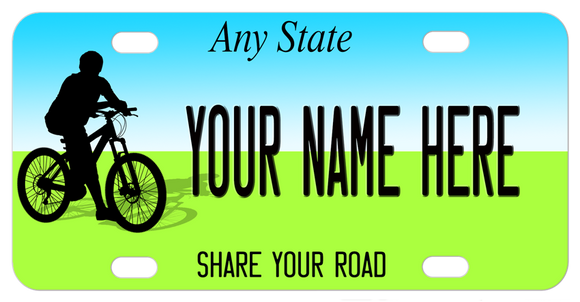 Bike Rider on bike plate with blue on top for sky and green on bottom for grass. Your state name on top and share the road on bottom