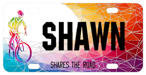 Fractured colors appearing like diamonds or stained glass pieces is the backdrop to a bike rider on these cool custom share the road license plates