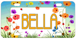 Pretty spring garden wild flowers surround your personalized name or monogrammed initials on a custom mini license plate