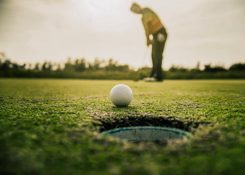 Golfer putting ball into the hole