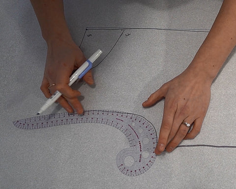 Use a French Curve Ruler to draft the armscye and necklines on the tee pattern