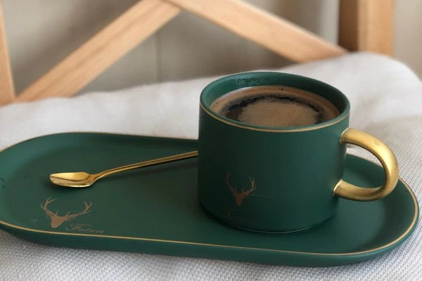Elk gold rim cup and suacer set on a table