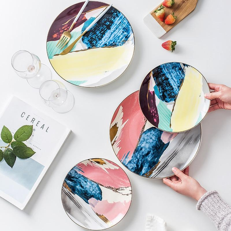 Four watercolor ceramic plates on a table