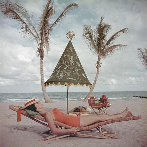 A photograph captured in 1955 of a young lady sunbathing in a one piece orange swimsuit on a lounge on the beach.