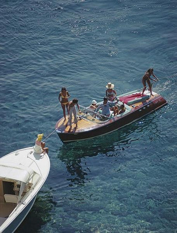 A photograph captured in 1969 of two small motor boats meeting together in the ocean with families enjoying the water.